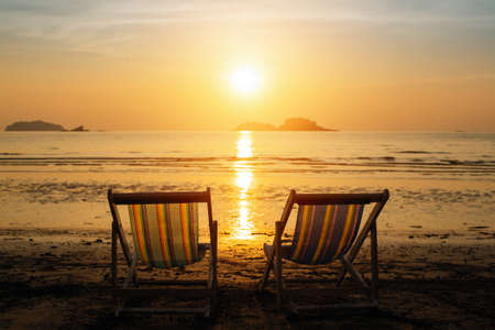 Sun loungers on the sea beach during amazing sunset.