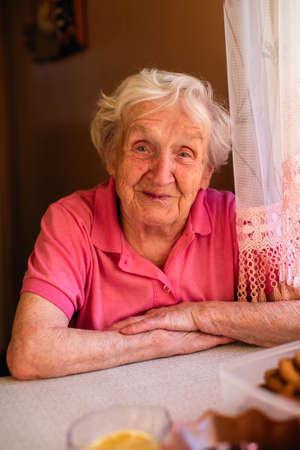 Abuela anciana bebe té en su casa. Retrato. Foto de archivo