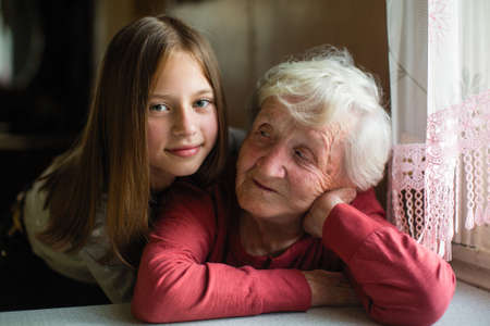 Portrait of little cute girl and her old grandmother.