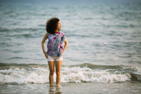 Young woman of mixed race stands on the surf line of sea. Imagens