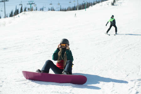 Girl with a snowboard sitting on a snowy slope.