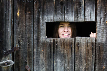 Young woman looks and smiles out the little window in the wooden shed.