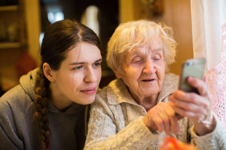 Elderly woman looks and typing on a smartphone, with his adult girl granddaughter. 写真素材