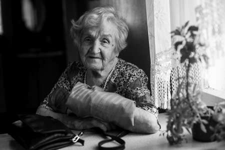 Portrait of an elderly lady at the table. Black and white photo. Banque d'images - 119848269
