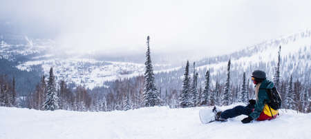 Panoramic picture of snowboarder sit in the mountains on a snowy slope.