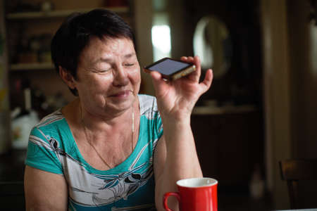 Mature woman fooling around with smartphone at rural home.