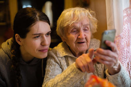 An old lady looks at a smartphone, with his adult granddaughter.