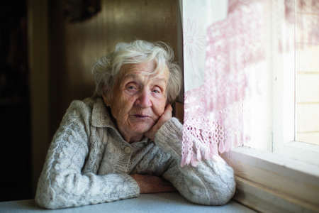 Gray haired elderly woman portrait at home.
