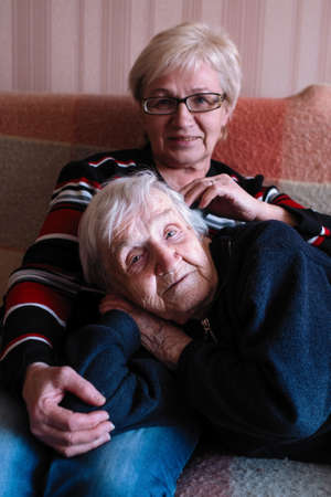 An old woman in an embrace with his adult daughter. 写真素材