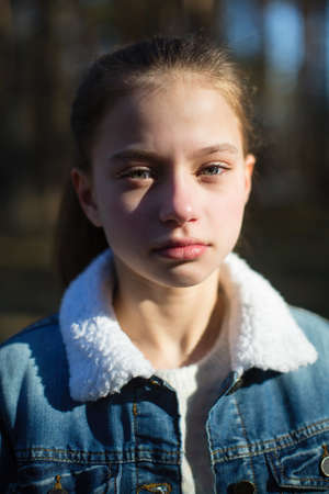 Closeup portrait of cute twelve year old girl outdoors.