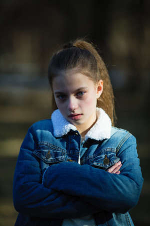 Portrait of cute twelve year old girl outdoors.