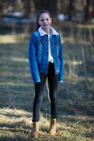 Full-length portrait of cute twelve year old girl in the park. 免版税图像