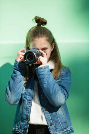 Cute twelve year old girl with camera stands near the green wall. Imagens