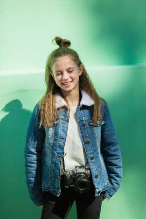 Cute twelve year old girl with camera stands near the green wall.