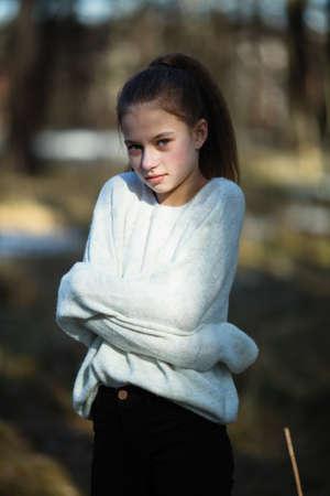 Linda niña de doce años en el parque posando para la cámara.