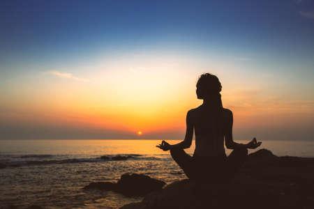 Sylwetka kobiety jogi w pozycji lotosu na brzegu oceanu wieczorem.