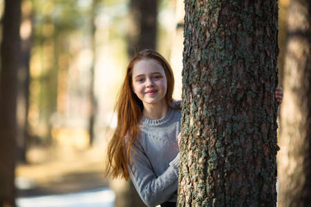 Twelve-year-old girl with long red hair posing in a summer pine Park. Imagens