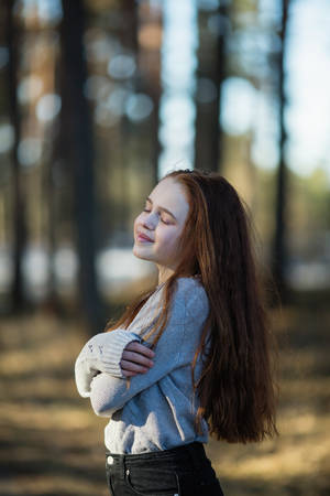 Twelve-year-old cute girl with long red hair posing for the camera in the park, photo shoot outdoors. Imagens