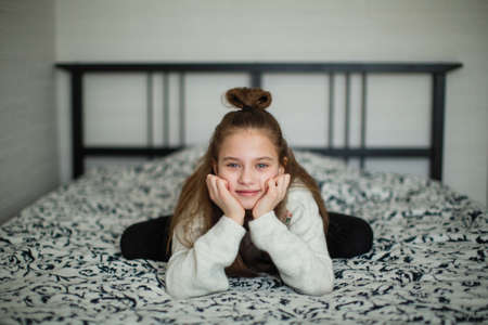 Twelve year old girl sitting having fun on the bed in her room.