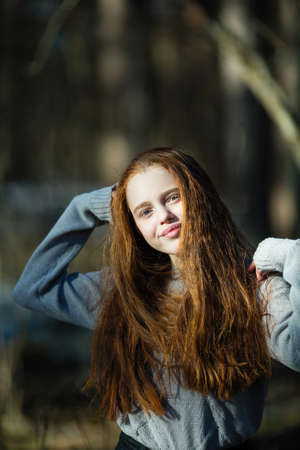 Portrait of cute twelve year old girl with fiery red hair posing in the pine park for a photoshoot. Imagens