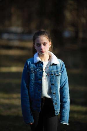 Retrato de una dulce niña de doce años con una chaqueta de mezclilla, sesión de fotos en el parque de primavera. Foto de archivo