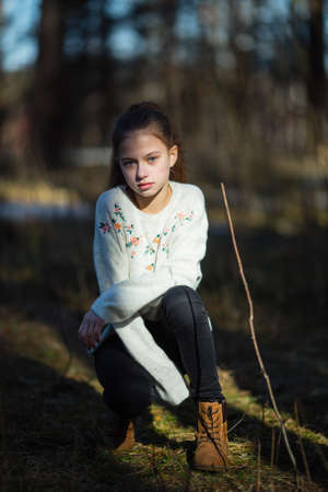 Portrait of a twelve-year-old sweet girl, photoshooting in the spring Park.
