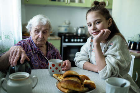 An old lady treats a little girl Breakfast, sitting at the table in his house. Grandmother and his lovely granddaughter.