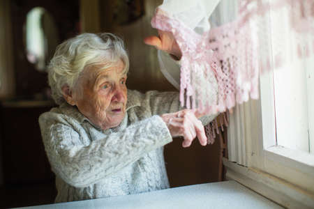 Portrait of an old elder woman looks and points her finger out the window. Pensioner in his house.