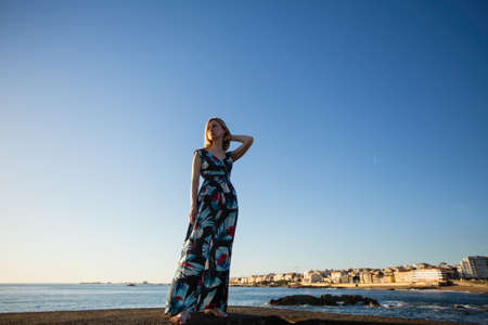 Beautiful blonde woman in a long dress standing on the seafront.