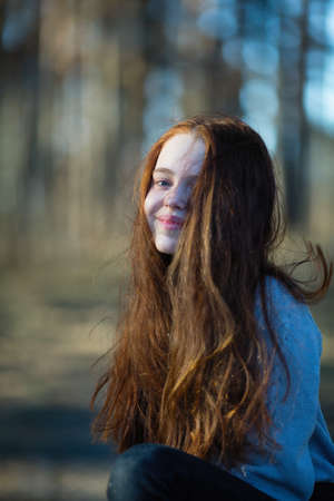 Red-haired little girl posing for a portrait in the Park. Imagens