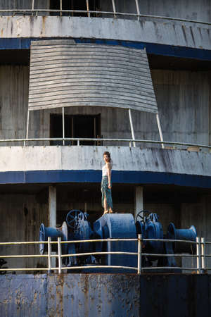 Asian young woman in the abandoned giant ship in jungle on the Islands in the Gulf of Thailand posing for a photoshoot.