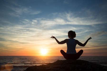 Silueta de mujer joven practicando yoga en la playa al atardecer. Foto de archivo