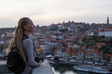 Young woman with dreadlocks on view point opposite Ribeira on Douro river, Porto, Portugal.