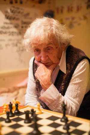 An old woman is playing chess.