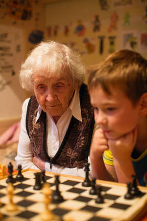An old lady is playing chess with her little grandson.