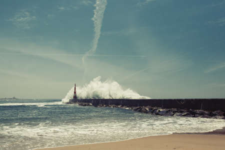 Lighthouse in the Miramar beach, powerful surf on the ocean coast, Portugal.
