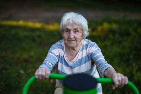 An old woman exercise on the street sport playground. Health of the elderly.