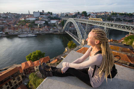 Young blond woman sitting on observation point opposite of Dom Luis I bridge in Porto, Portugal. Imagens
