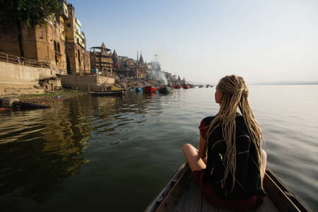 Tourist woman on a boat glides through the water on the Ganges river, Varanasi, India.