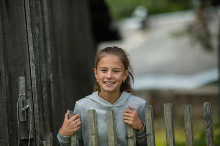 Teen girl near the wooden fence at village.