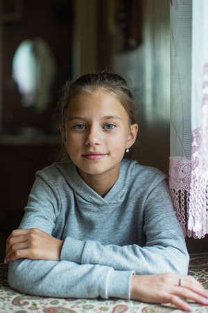 Retrato de una linda niña de doce años sentada en la mesa. Foto de archivo