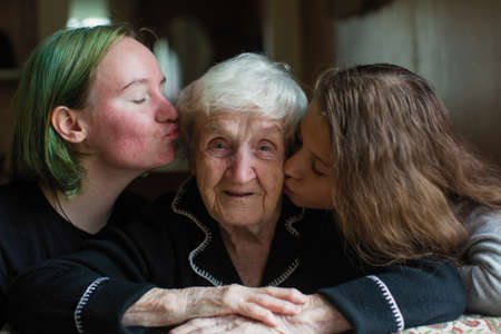 Two girls granddaughter kissing her grandmother.