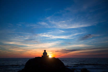 Silhouette of a lonely man sitting on the rocks near the ocean beach during the amazing sunset.