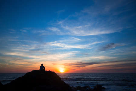 Silhouette of a lonely man sitting on the rocks at ocean beach during amazing sunset. Stock Photo
