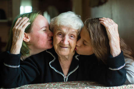 Two girls granddaughter kissing the cheeks of his old grandmother.