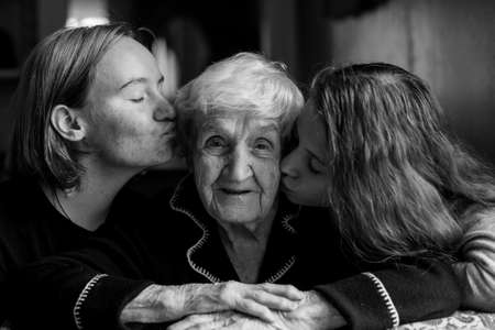 Two girls granddaughter kissing the cheeks of his old grandmother. Black and white photo.