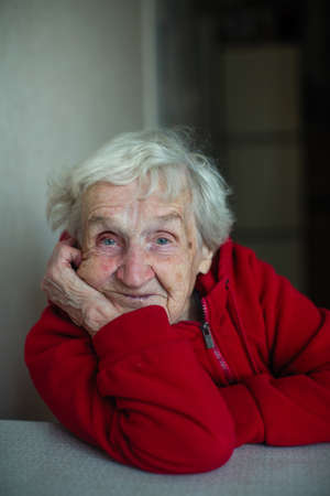 Very old woman in her house, close-up portrait sitting at a table in a red jacket. Plight of pensioners.