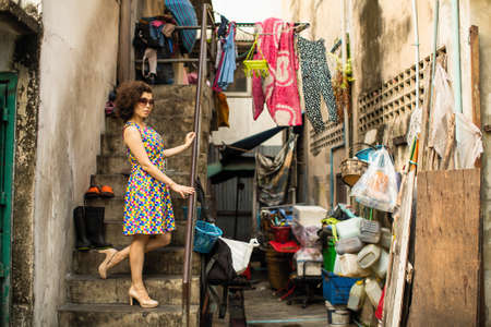 Asian woman stands in the slums of the street.