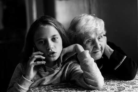 An grandmother listens as great-granddaughter talks on the phone. Black and white photo.