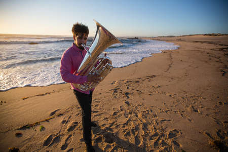 Man musician with a tuba playing on the ocean beach. Standard-Bild